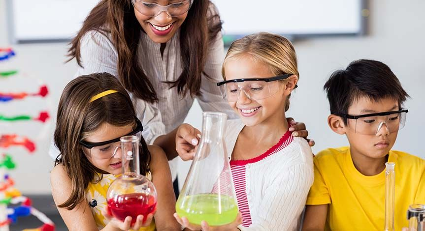 2 girls holding beakers and a boy looking down while teacher points to one of the beakers.