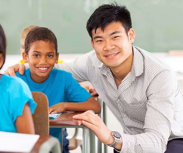 Boy sitting at desk with his teacher who has his arm around the student