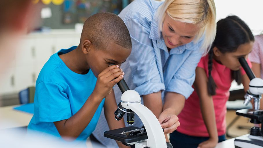 Kids looking through a microscope while teacher helps the student