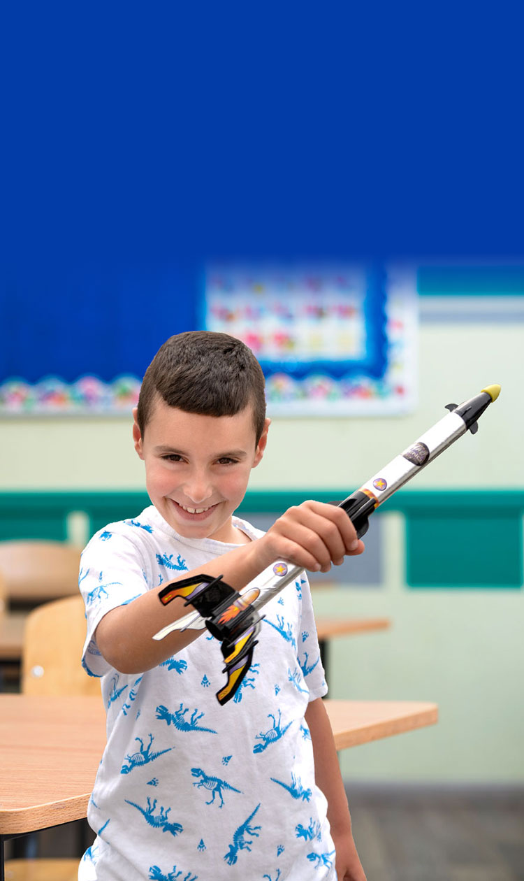 Boy smiling in a classroom while playing witha toy spaceship
